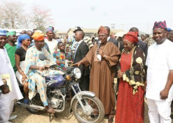 Executive Governor of Oyo state Sen Ajimobi presenting Motorcyc;le to  a beneficiaies while Sen Sumonu and  Hon Akeem Adeyemi watches.