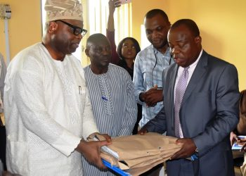 The Secretary to the Oyo State Government, Mr. Olalekan Alli receiving the project documents at the handing over of buildings donated by CBN to TechU, Ibadan from the CBN Branch Controller, Lagos Branch, Mr. Omebere Iyari on Thursday in Ibadan.