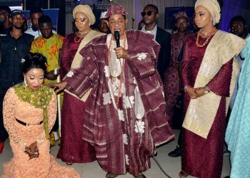 His Imperial Majesty Oba Lamidi Olayiwola Adeyemi flanked by two olori  praying for Lizzy Anjorin