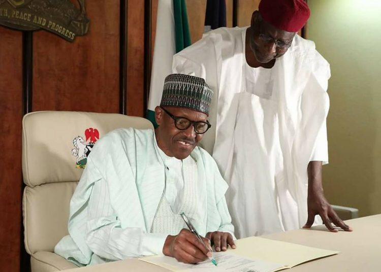 President Buhari signing a letter