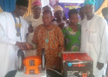 Rotary club Agodi new president Barr Kazeem Oladepo,  flanked by community service director Engr Adeleye Gbenga  presenting equipment to the cobbler in Ibadan