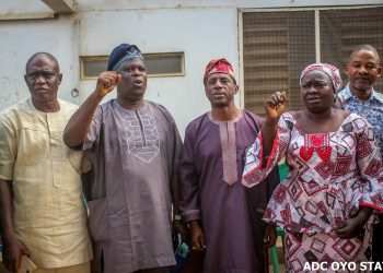 Comrade Abdulwaheed Olojede, Oyo State NLC Chairman, leading solidarity songs, in a group photograph with Senator Olufemi Lanlehin. With them is Arch Basiru Lawal, DG, Handshake Campaign Organisation (HCO), and another union official