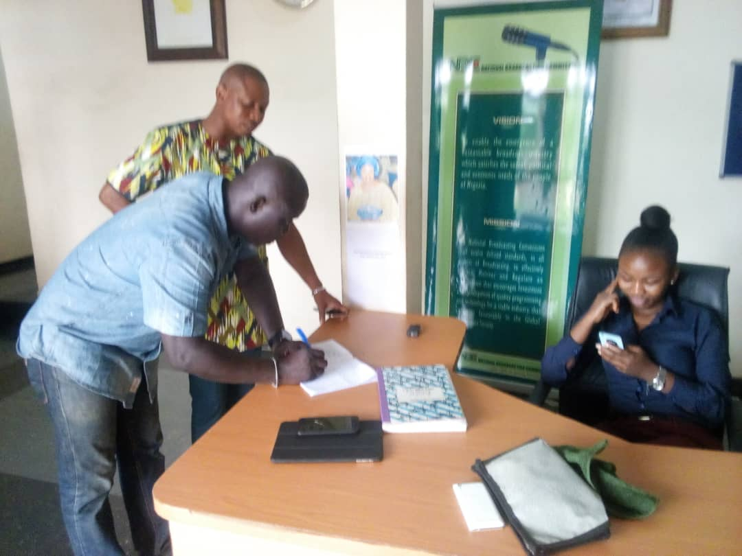 Caption: Oyo SWAN Chairman Mr Niyi Alebiosu signing the condolence register placed for the late Zonal Director at the NBC Zonal office in presence of a Senior NBC Monitoring Officer, Mr Akin Akinwale