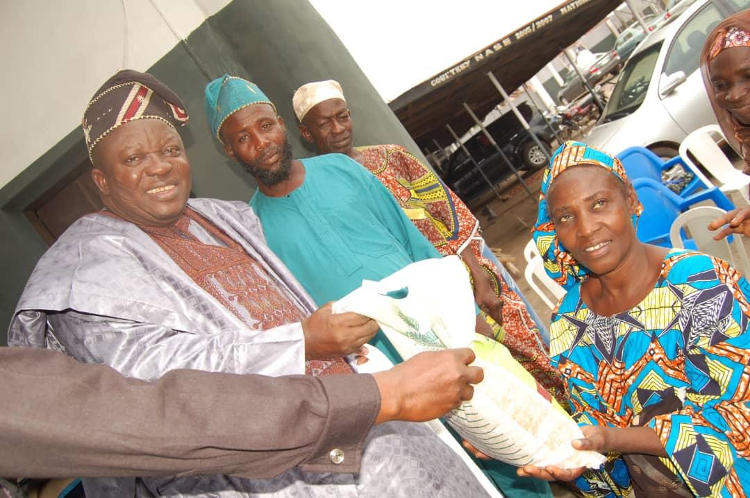 Okere of Saki Oba Khalid Olabisi, Oyedepo 111 presenting food items to one of the beneficiaries
