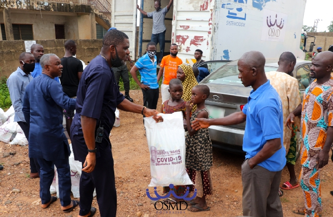 Bisyoye Fagade  handing out a  pack  of  the food items to beneficiaries