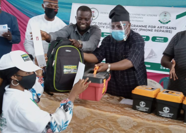 caption. Chairman Senate Committee on Land Transport Senator Buhari Abdulfatai joined by representative of NITDA DG Alhaji Inuwa Abdulahi to present an mobile tablets, tool kit and statrt up cash to one of the participants at the closing ceremony of training on Digital economy for Artisans in Oyo organized by NITDA