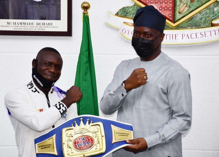 """Oyo State Governor, Engr Seyi Makinde (right) and World Boxing Federation's Super Featherweight Champion, Ridwan  Oyekola """"Scorpion"""" (middle) from Oyo State, during the presentation of his Belt to the Governor, why Co-Chairman and President, Nigeria Boxing Board of Control, Dr Rafiu Ladopo look-on at Governor's Office, Secretariat, Ibadan. PHOTO: Oyo State Government."""