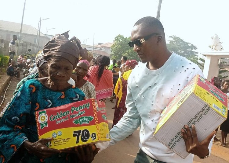 Mr Tijani Usman presenting a pack  of noodles to an aged woman